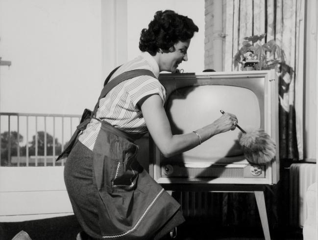 Een huisvrouw met schort aan is met een plumeau bezig een TV / televisietoestel af te stoffen. LET OP! Dit is een minimaal bewerkt lowres bestand. Wilt u een groter en/of bewerkt bestand neem dan contact op met 023-5185150 of verkoop@spaarnestadphoto.nl.